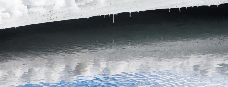 Is og dråper speiler seg i elva.